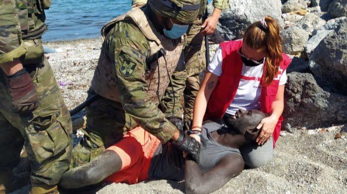 Miembros del Ejército de Tierra y de la Cruz Roja ayudan a un inmigrante que han logrado cruzar uno de los espigones fronterizos de Ceuta este martes en una avalancha de inmigrantes sin precedentes en España al registrarse la entrada en 24 horas de 5 000 personas (un tercio de ellas menores). Foto: EFE