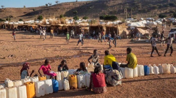 Refugiados esperan para cargar agua en bidones, en el campo de refugiados de Um Rakuba, ubicado en  Sudán, cerca de la frontera con la región etíope de Tigray. Foto: Thomas Dworzak/Magnum Photos