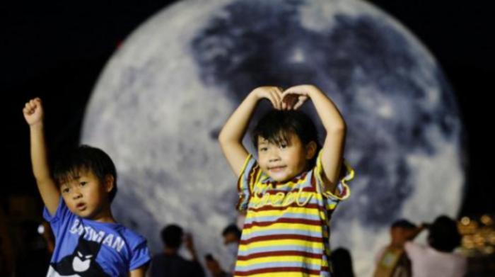 Niños frente a un globo gigante con forma de luna antes del Festival de Medio Oriente. Foto: Reuters