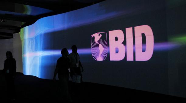 Los visitantes pasan por delante de una pantalla con el logo del Banco Interamericano de Desarrollo (BID). Foto: Archivo / Reuters