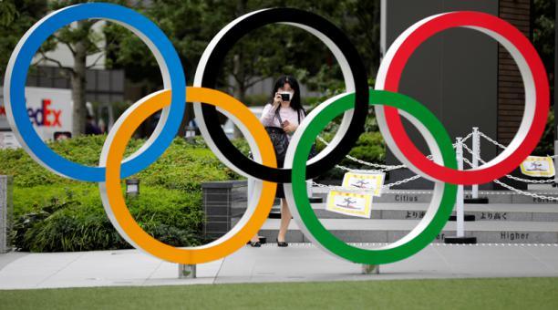 Una mujer utilizando mascarilla toma una fotografía a os anillos olímpicos frente al Estadio Nacional de Tokio