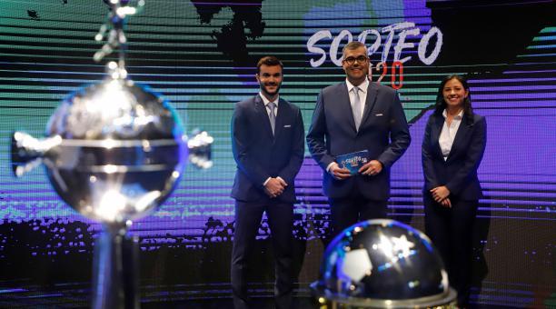 El director de competiciones de Clubes Conmebol, Frederico Nantes (c), posa junto a los trofeos de la Copa Libertadores y Sudamericana en el sorteo de las siguientes fases hoy, en la sede del Conmebol en Luque (Paraguay). EFE