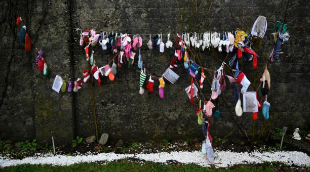 Calcetines para niños y otros artículos cuelgan de una pared en el cementerio de Tuam, donde los cuerpos de 796 bebés fueron descubiertos en el sitio de un antiguo hogar católico para madres solteras y sus hijos el día en que una investigación ordenada po
