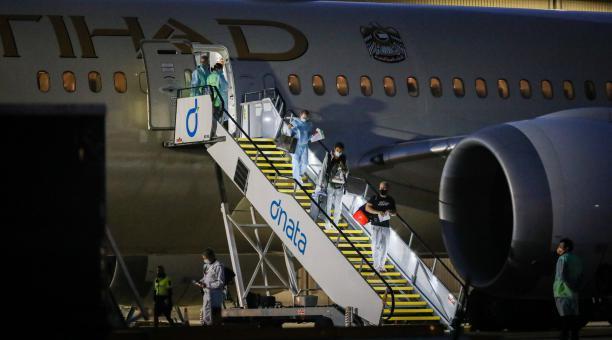 Los pasajeros del avión que llegó desde Doha a Melbourne descienden para ser sometidos  pruebas covid. Foto: EFE