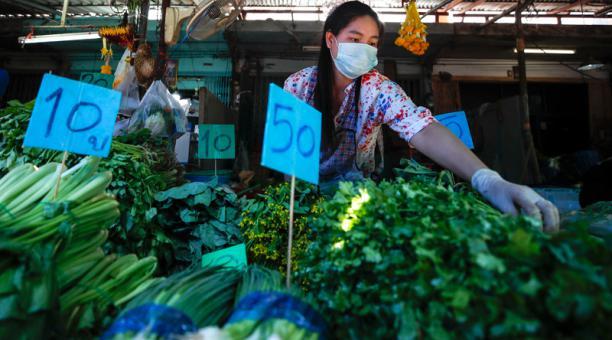 Un comerciante con una mascarilla protectora arregla verduras en un mercado húmedo en Bangkok, Tailandia, el 13 de enero de 2021.