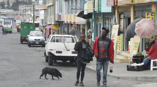 Dos personas que no usan correctamente la mascarilla caminan en el barrio Julio Zabala, parroquia de Calderón. Foto: Eduardo Terán / EL COMERCIO