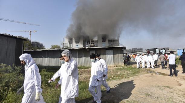 Trabajadores indios están afuera después de que estalló un incendio en un edificio de las instalaciones de Pune del Serum Institute of India, fabricante de vacunas de Covid, en Pune Maharashtra, India, el 21 de enero de 2021.