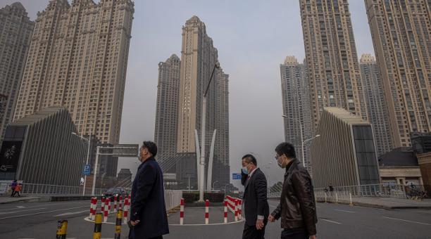 Personas con máscaras protectoras cruzan una calle de Wuhan