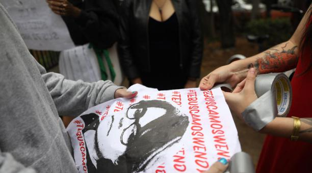 Una mujer sostiene un cartel con el mensaje