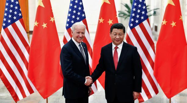 El presidente chino, Xi Jinping, estrecha la mano del actual presidente estadounidense, Joe Biden (izq.), en el interior del Gran Salón del Pueblo, en Pekín, el 4 de diciembre de 2013