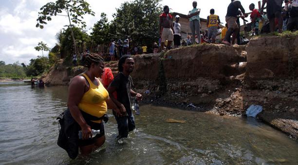 Migrantes haitianos caminan a través del río turquesa hacía la comunidad de Bajo Chiquito, tras caminar desde Colombia