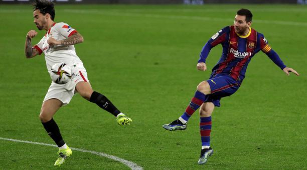 El delantero argentino del FC Barcelona, Leo Messi (d), golpea el balón ante el centrocampista del Sevilla, Jesús Joaquín Fernández