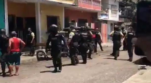 Un grupo de ciudadanos y miembros de la Policía se enfrentan durante un operativo para desmontar piscinas en Guayaquil, este 16 de febrero del 2021. Foto: Captura