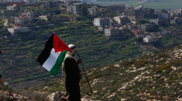 Un hombre palestino ondea la bandera palestina durante una manifestación contra los asentamientos de Israel en la aldea de Bet Dajan, cerca de la ciudad de Naplusa, en el norte de Cisjordania, el 26 de febrero de 2021.