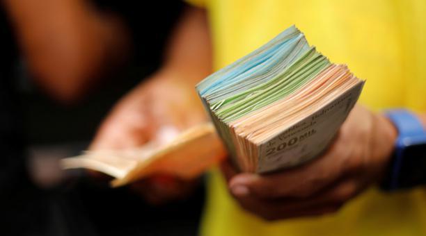 Un asistente de un conductor de buses sostiene un fajo de billetes de bolívares después de que el gobierno lanzó una circulación billetes de mayor denominación, en Caracas, Venezuela, 16 de marzo de 2021. Foto: REUTERS