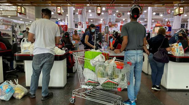 Varias personas pagan sus productos en las cajas registradoras de un supermercado el 11 de marzo de 2021, en Caracas. Foto: EFE.