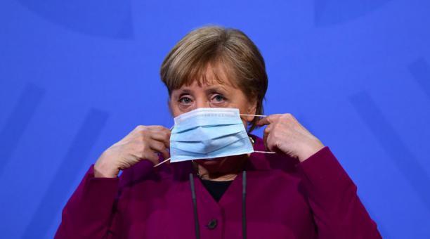 La canciller alemana Angela Merkel se pone una mascarilla tras hablar con los medios de comunicación en la Cancillería de Berlín, Alemania, el 25 de marzo de 2021. Foto: EFE