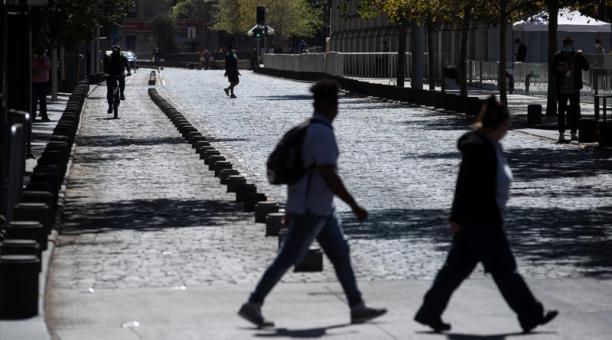 Personas cruzan una calle hoy, en Santiago (Chile). Chile se prepara para un fin de semana de megacuarentena, con el 97 % de la población confinada y los permisos para ir a comprar suspendidos
