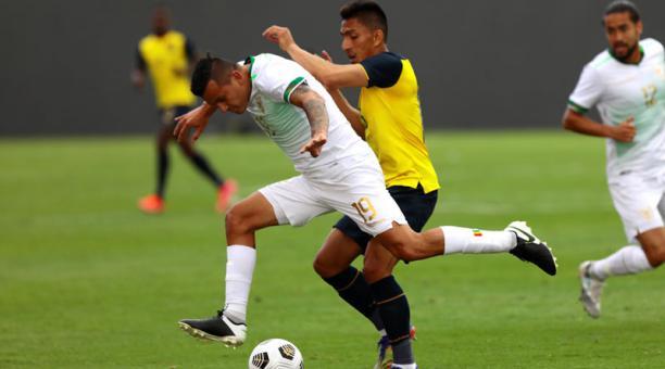 Ángel Mena (c) de Ecuador disputa un balón con Enrique Flores de Bolivia el 29 de marzo del 2021. Foto: EFE