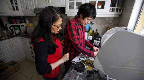 María de Lourdes Ortega y su hijo Dani Briceño, de 22, quien prepara la comida. Foto: Patricio Terán/ EL COMERCIO