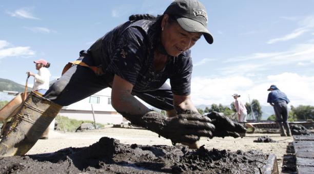 María Quishpe, de 59 años, pone la mezcla para elaborar ladrillos en los moldes que dejan al sol. Fotos: Patricio Terán / EL COMERCIO