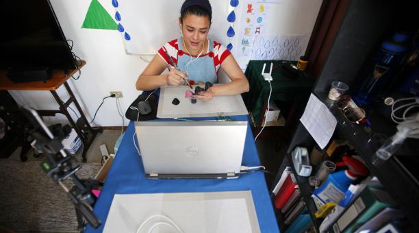 Natalia Figueroa, conectándose al Internet de una prima, que vive en una casa vecina, brinda clases. Foto: Patricio Terán/ EL COMERCIO