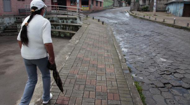 La líder Azucena Ortiz camina por la calle mojada en Libertad de Chillogallo. Foto: Galo Paguay / EL COMERCIO
