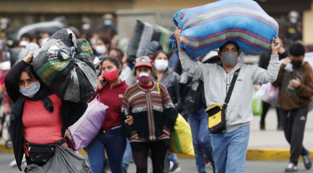 Vendedores ambulantes que se desplazan luego de ser desalojados por la Policía de un sitio donde vendían sus productos, en Lima (Perú). Foto: EFE
