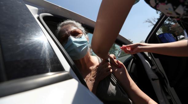 Una trabajadora de la salud administra una dosis de la vacuna CoronaVac contra el COVID-19 en un centro de vacunación en automóviles, en Santiago, Chile, Febrero 26, 2021.