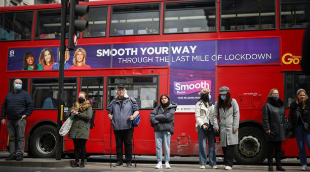 Foto del lunes de un grupo de personas esperando para cruzar una calle en Londres en la jornada de inicio del alivio de las restricciones por la pandemia de coronavirus.