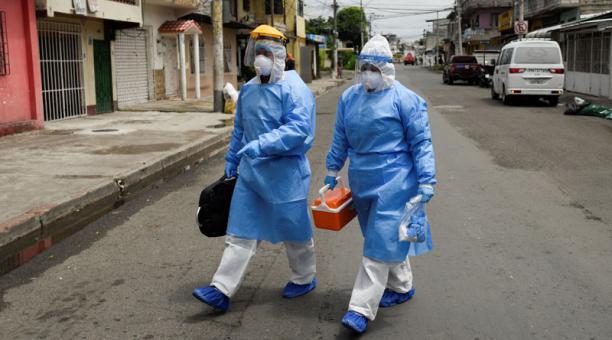 Médicos del Ministerio de Salud ecuatoriano caminan a una residencia para tomar muestras de personas que se sospecha tienen covid-19. Foto: REUTERS