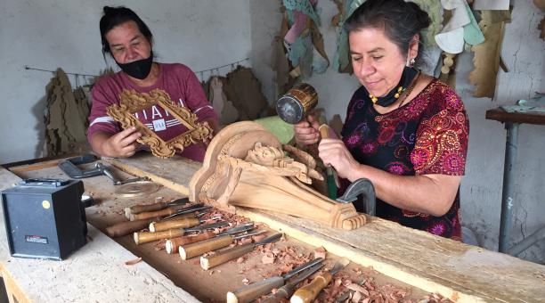María Yépez (izq.) mira cómo su hermana Rosa diseña una figura en el taller familiar. Foto: Washington Benalcázar / EL COMERCIO