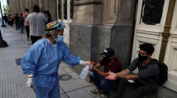 Una trabajadora de la salud sanitiza a personas con mascarillas que esperan en una fila para hacer la prueba de covid-19 en Buenos Aires, Argentina, el 13 de abril de 2021. Foto: REUTERS