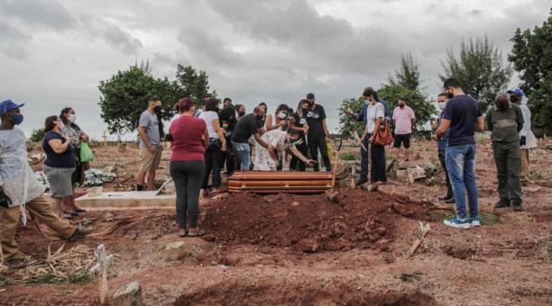Familiares lloran la muerte por covid-19 de un ser querido, durante su entierro, en un cementerio del norte de Río de Janeiro (Brasil). Foto: EFE