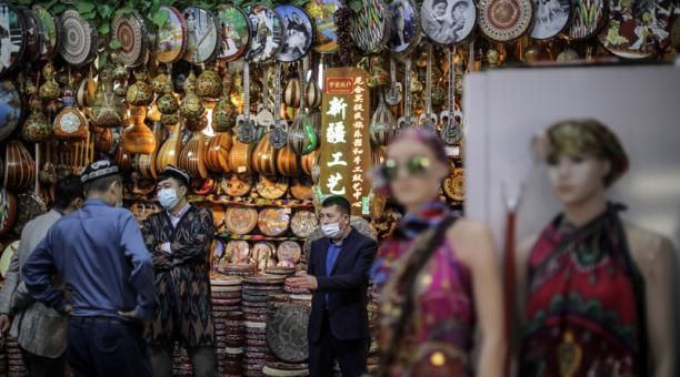 Vendedores charlan en un puesto del Gran Bazar Internacional en Urumqi, región autónoma uigur de Xinjiang, en el oeste de China. Foto: EFE