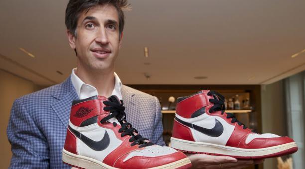 Josh Pullan, director gerente de la División de Lujos Global de Sotheby's sostiene un par de 'Air Jordan 1' usadas por el campeón Michael Jordan en Ginebra, Suiza, 28 de abril del 2021. Foto:  REUTERS