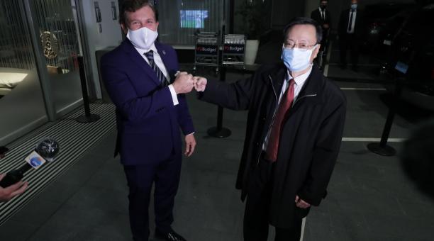 El presidente de la Confederación Suramericana de Fútbol (Conmebol), Alejandro Domínguez (i), y el embajador de China en Uruguay, Wang Gang, se saludan durante la llegada de un cargamento con 50.000 vacunas donadas a esa institución por la farmacéutica ch