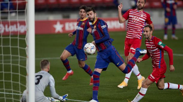 El defensa del FC Barcelona Gerard Piqué (c) remata un balón ante el portero Aarón Escandell (i), del Granada, durante el partido de Liga en Primera División disputado este jueves en el Camp Nou, en Barcelona. EFE