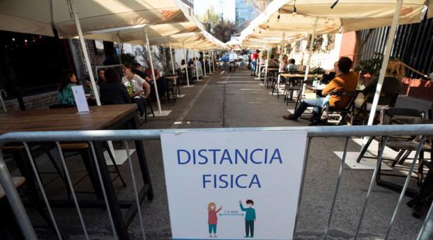 Vista de un aviso de distanciamiento físico en una terraza en la que un grupo de personas disfrutan de un almuerzo en Santiago (Chile). Foto: EFE