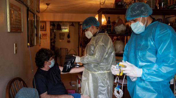 Paramédicos evalúan a un paciente que se recupera del covid-19 en su domicilio en Caracas (Venezuela). Foto: EFE