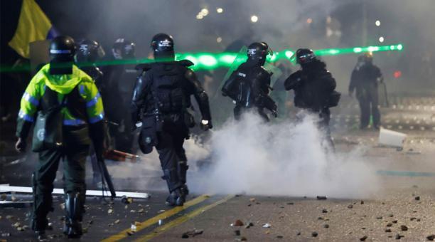 Integrantes del Escuadrón Móvil Antidisturbios (ESMAD) se enfrentan a manifestantes que llegan al barrio donde tiene su residencia el presidente de Colombia Iván Duque, durante una jornada de protestas contra la reforma tributaria, hoy en Bogotá (Colombia