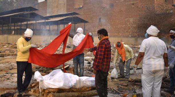 Se prepara un cuerpo para los últimos ritos en piras funerarias para las víctimas de covid-19 en Nueva Delhi, India. Foto: EFE