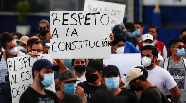 Manifestantes sostienen carteles que dicen
