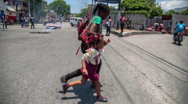Una madre corre hoy junto a hija durante protestas contra el proyecto de Constitución que impulsa el presidente Jovenel Moise y contra la ola de violencia y secuestros que sacude al país, en Puerto Príncipe (Haití).