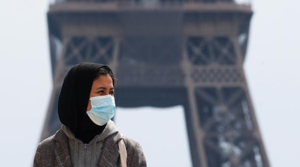 Una mujer con hiyab y mascarilla anda por la plaza de Trocadero, junto a la torre Eiffel de París, Francia. 2 mayo 2021.