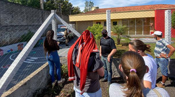 Varias personas esperan afuera de una guardería donde tres bebés fueron asesinados por un adolescente en Saudades, Santa Catarina, Brasil, el 4 de mayo de 2021. Foto: EFE