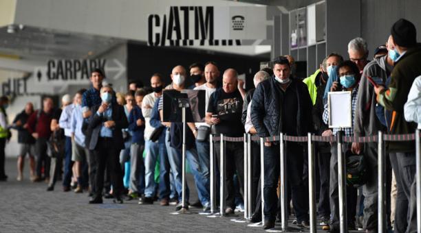 Las personas esperan en la fila para vacunarse contra el covid-19 en el Centro de Convenciones y Exposiciones de Melbourne. Foto: EFE