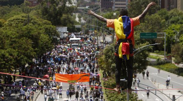Un hombre realiza acrobacias frente a cientos de personas que marcharon el miércoles 5 de mayo del 2021 en una nueva jornada de protestas en el marco del Paro Nacional, en Medellín (Colombia). Foto: EFE