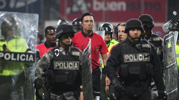 El árbitro Vinicio Espinel es escoltado tras el partido entre Independiente del Valle y Barcelona. Foto: EL COMERCIO