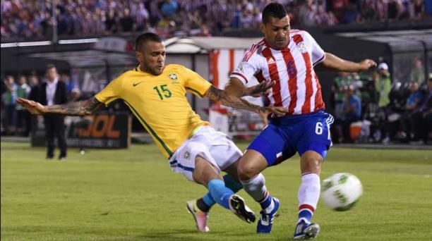El brasileño Daniel Alves busca la pelota ante el paraguayo Miguel Samudio el 29 de marzo en Asunción. Foto: Pablo Burgos/ AFP